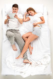 Les jeunes beaux couples se situant dans un lit avec l'ordinateur portable Photographie stock libre de droits