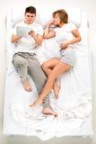 Les jeunes beaux couples se situant dans un lit avec l'ordinateur portable Photographie stock
