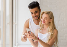 Les jeunes beaux couples se tiennent près de la grande fenêtre, utilisant la femme hispanique d'homme de sourire heureux futé de  Photos stock