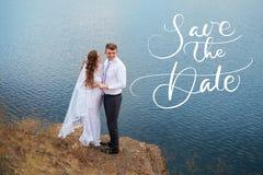 Les jeunes beaux jeunes mariés de couples à la promenade de mariage par le lac et les mots font gagner la date Lettrage de callig Photographie stock libre de droits