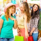 Les jeunes belles amies de femmes aux achats de marché aux puces vêtx Images stock