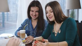Les jeunes belles amies s'asseyant dans un café parlent et rient Les filles mignonnes boivent du café et du latte banque de vidéos