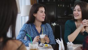 Les jeunes belles amies s'asseyant dans un café parlent et rient Les filles mignonnes boivent du café et du latte clips vidéos