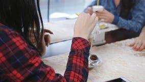Les jeunes belles amies s'asseyent dans un café par la fenêtre et le latte de boissons Les filles mignonnes rient, parlent et boi clips vidéos