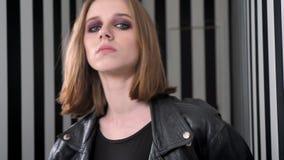 Les jeunes belles femmes avec lourd composent dans la veste noire regardant in camera, fond sûr et rayé de mur banque de vidéos