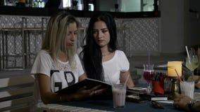 Les jeunes belles filles dans le club s'asseyant à un restaurant ajournent l'essai de décider ce qui à l'ordre du menu clips vidéos