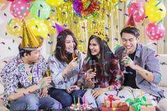 Les jeunes boivent du champagne à la fête d'anniversaire image stock
