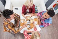 Les jeunes boivent le café, amis reposant le sourire de table Photos libres de droits