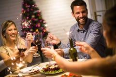 Les jeunes célébrant la nouvelle année et buvant du vin rouge Photo libre de droits