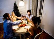 Les jeunes célébrant la nouvelle année et buvant du vin rouge Photographie stock libre de droits