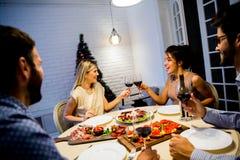 Les jeunes célébrant la nouvelle année et buvant du vin rouge Images libres de droits