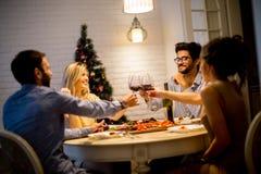 Les jeunes célébrant la nouvelle année et buvant du vin rouge Images stock