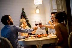 Les jeunes célébrant la nouvelle année et buvant du vin rouge Image libre de droits