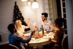 Les jeunes célébrant la nouvelle année et buvant du vin rouge Photographie stock