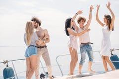 Les jeunes caucasiens heureux dansant dans le bateau font la fête Photographie stock