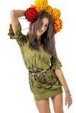 Les jeunes cheveux gais minces de brun de fille dansent avec un bouquet des fleurs colorées sur sa tête Images libres de droits