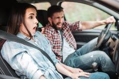 Les jeunes conduisent très rapide ils font un arrêt inattendu Le type est criard tandis que la fille garde sa bouche Photographie stock libre de droits