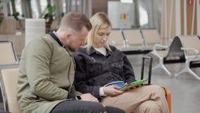 Les jeunes conjoints s'asseyent ensemble dans le salon de départ et regardent sur le comprimé banque de vidéos