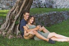 Les jeunes couplent dans l'amour se reposant sous un arbre dans un château photo stock