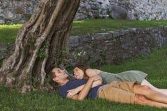 Les jeunes couplent dans l'amour se reposant sous un arbre dans un ch?teau photographie stock libre de droits