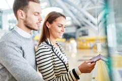 Les jeunes couples à l'aéroport vérifient dans le compteur image stock