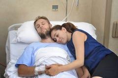 Les jeunes couples à la chambre d'hôpital équipent se situer dans la femme inquiétée par lit tenant ses soins de main Images stock