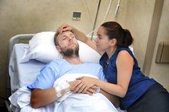 Les jeunes couples à la chambre d'hôpital équipent se situer dans la femme inquiétée par lit tenant ses soins de main Images libres de droits