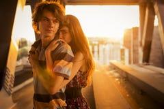 Les jeunes couples étreignant dans les fusées du coucher du soleil s'allument sur un pont c Photographie stock