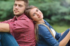 Les jeunes couples adultes situant de retour soutiennent dedans en nature photographie stock libre de droits