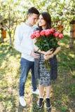 Les jeunes couples affectueux dans l'amour, la fille tenant des fleurs, heureuses et apprécient la beaux nature, publicité, et te Photos libres de droits