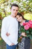 Les jeunes couples affectueux dans l'amour, la fille tenant des fleurs, heureuses et apprécient la beaux nature, publicité, et te Photo libre de droits