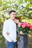 Les jeunes couples affectueux dans l'amour, la fille tenant des fleurs, heureuses et apprécient la beaux nature, publicité, et te Photographie stock libre de droits