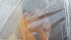 Les jeunes couples affectueux se tiennent sous un parapluie sous la pluie banque de vidéos