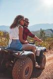 Les jeunes couples appréciant un vélo de quadruple montent dans la campagne Photo stock