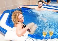 Les jeunes couples apprécient et détendent au centre de station thermale images libres de droits