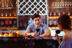 Les jeunes couples asiatiques équipent ensemble et les verres de tintement de femme Images stock