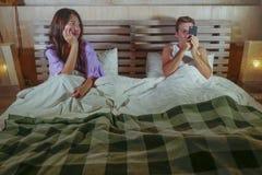 Les jeunes couples asiatiques et caucasiens mélangés attrayants dans le lit avec le media social s'adonnent à l'homme à l'aide du Photographie stock libre de droits
