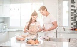 Les jeunes couples asiatiques heureux font des boulangers aidant à faire la boulangerie voir le comprimé de forme de recettes image libre de droits