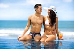 Les jeunes couples asiatiques s'approchent de la piscine Image libre de droits