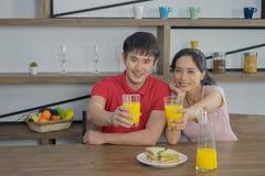 Les jeunes couples asiatiques, se reposent à la table de salle à manger ils sont heureusement sourire avec boire du jus d'orange photos libres de droits