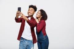 Les jeunes couples attrayants d'Afro-américain posent pour la pose de selfie avec le téléphone intelligent Image stock
