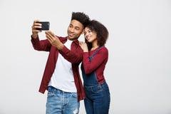 Les jeunes couples attrayants d'Afro-américain posent pour la pose de selfie avec le téléphone intelligent Photographie stock libre de droits