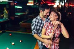 Les jeunes couples attrayants la date dans le billard matraquent Photographie stock