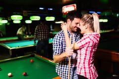 Les jeunes couples attrayants la date dans le billard matraquent Photographie stock libre de droits