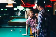 Les jeunes couples attrayants la date dans le billard matraquent Images stock
