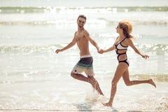 Les jeunes couples attrayants ont l'amusement sur la plage image stock