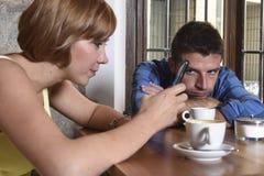 Les jeunes couples au café avec l'Internet et le téléphone portable s'adonnent à la femme ignorant l'homme frustrant Photos stock