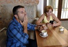 Les jeunes couples au café avec l'Internet et le téléphone portable s'adonnent à la femme ignorant l'homme frustrant Photo libre de droits