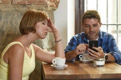 Les jeunes couples au café avec l'intoxiqué d'Internet et de téléphone portable équipent ignorer la femme frustrante Image libre de droits