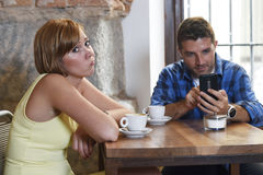 Les jeunes couples au café avec l'intoxiqué d'Internet et de téléphone portable équipent ignorer la femme frustrante Images stock